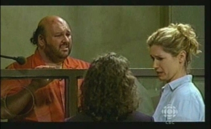 Still photo from television show set. Jo is playing a character in a court room.